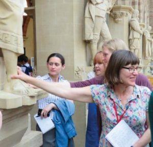 Exploring the built environment as part of training at OUMC. Photograph showing trainees visiting a building containing multiple stone statues.