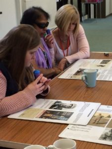 Visitors and Conan Doyle touring exhibition. Photograph of visitors seated around a table listening to audio descriptions of panels laid out on a table in front of them.