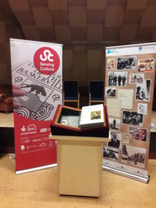 "Conan Doyle sensory exhibition (case inc. fridge). Photograph of the plinth on which the open ""book"" containing the 3D models and the tactile panels sits. Behind the plinth and to either side are two large banners advertising the exhibition. On the left-hand banner is the ""Sensing Culture"" logo superimposed upon an image of a braille version of ""The Hound of the Baskervilles"". On the right-hand banner are photographs and images relating to Conan Doyle and to Sherlock Holmes"
