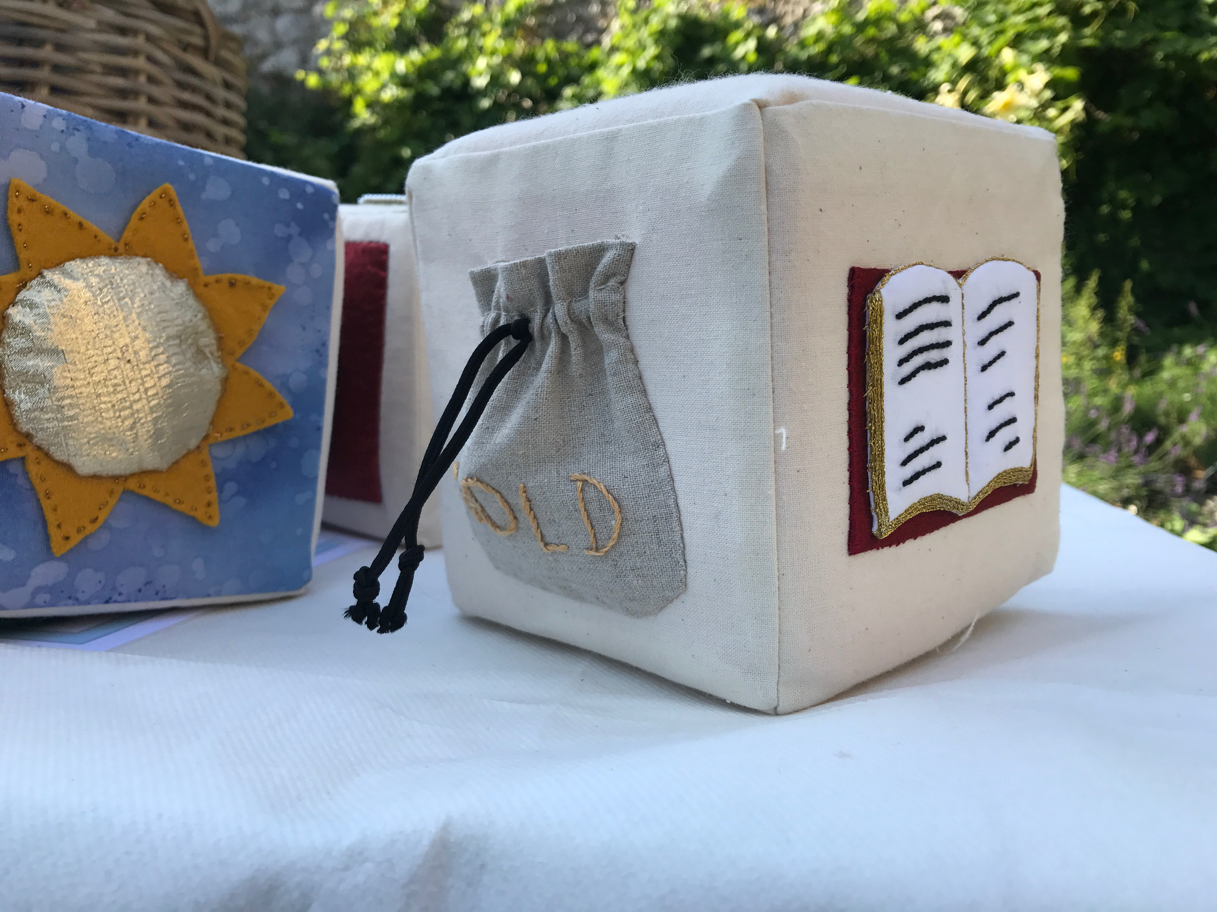 """Lewes Castle story cubes. Photograph of fabric-covered cubes. On each face of each cube is sewn a tactile representation for the different aspects of a story, for example a """"gold"""" pouch and an open book on one cube, and a golden sun on another"""