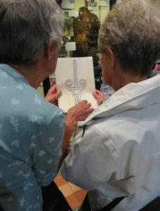 Oxford touch tour. Photograph of two women viewing/tracing their hands over a tactile image