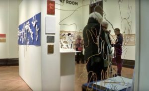 Beaney Canterbury—Exhibition. Photograph showing visitors to the exhibition. Tactile art hangs on the walls and there is a free-standing display of wire artwork.