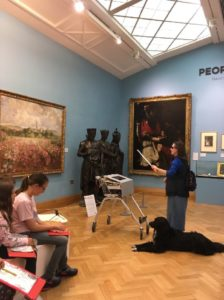 Beaney Butterfly Machine. Photograph showing a BPS visitor to the gallery using the Machine. The Machine is positioned in front of a large painting of a landscape and the visitor directs the baton towards the painting. Her guide dog waits patiently beside her.]