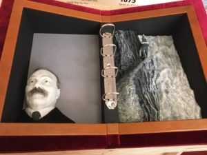 "Conan Doyle sensory exhibition book. Photograph of an open ""book"" containing 3D items for handling—on the left-hand side is a model of Conan Doyle's head and shoulders with an embossed ""Spirit"" appearing over the model's left shoulder; on the right-hand side is a model of Holmes and Moriarty battling on the cliffs over the Reichenbach Falls"